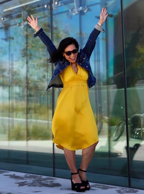 Woman in yellow dress reaching skyward